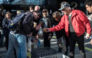 Glad volontär ger bröd till besökare